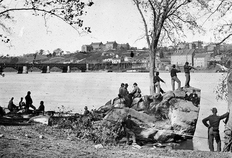 Union soldiers guarding the Potomac River in 1861. Behind them is the old Aqueduct bridge and Georgetown University on top of the hill
